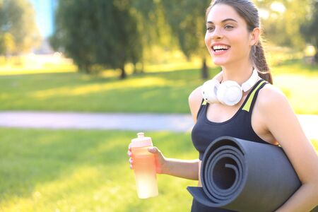 Beautiful happy young sports woman holding fitness rug in urban park