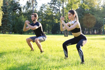 Young sporty man and woman doing workout and squatting together in green park during summer sunny day