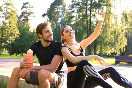 Young sporty couple in sportswear sitting on parapet in urban park and taking selfie after workout on summer sunny day. Stock Photo