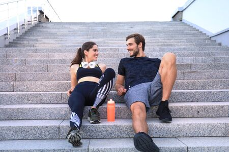 Young couple in sportswear sitting on the stairs after exercising outdoors