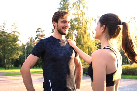 Happy young sport couple talking while standing in park