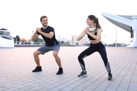 Young sporty man and woman doing workout and squatting together on urban street at sunset or sunrise