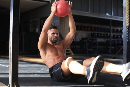 Fit and muscular man exercising with medicine ball at gym