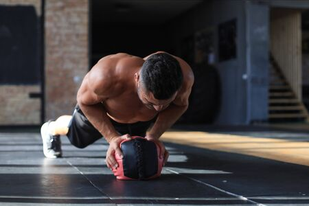 Homme en forme et musclé s'exerçant avec médecine-ball au gymnase