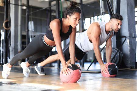 Hermosa joven pareja de deportes está trabajando con balón medicinal en el gimnasio