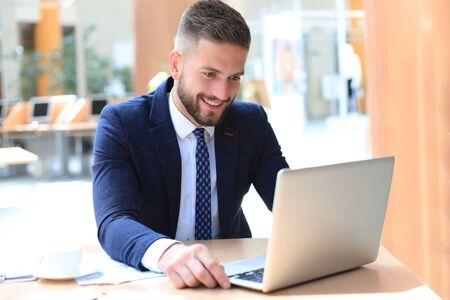 Hombre sonriente sentado en la oficina y usando su computadora portátil Foto de archivo