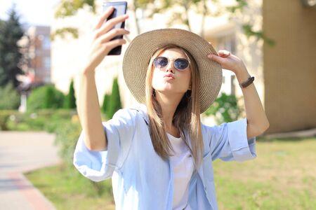 Mooie jonge blonde meid die mobiele telefoon gebruikt terwijl ze buiten staat