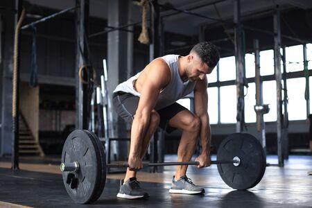 Muskulöser Mann, der im Fitnessstudio trainiert und Übungen mit der Langhantel am Bizeps macht