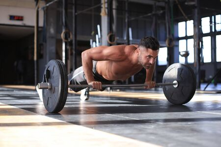 Fit and muscular man doing horizontal push-ups with barbell in gym