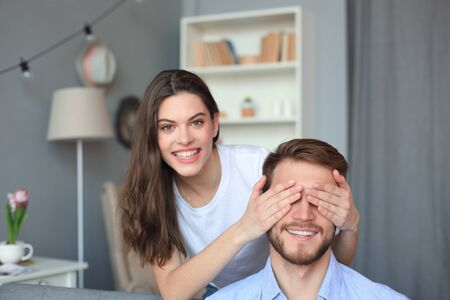 Young cute woman covering her husband's eyes Stock Photo