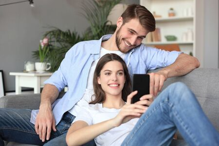 Young couple watching online content in a smart phone sitting on a sofa at home in the living room