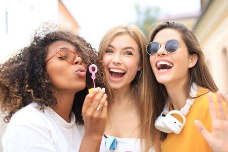 Three happy beautiful women blowing soap bubbles in city street