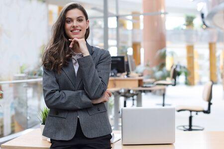 Attraktive Geschäftsfrau, die in der Nähe des Schreibtisches im Büro steht Standard-Bild