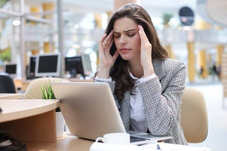 Frustrated business woman looking exhausted while sitting at her working place.