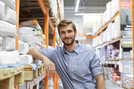 portrait of a smiling young warehouse worker working in a cash and carry wholesale store Stockfoto