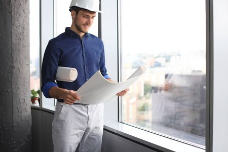Confident young business man in hardhat holding blueprint and looking away while standing indoors