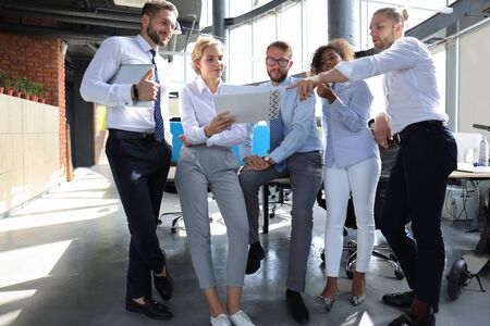 Groep moderne zakenmensen praten en glimlachen terwijl ze op kantoor staan.