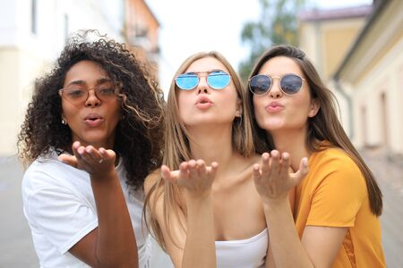 Three beauty women wearing summer clothes posing togeher in tke city and looking at the camera, sending kiss