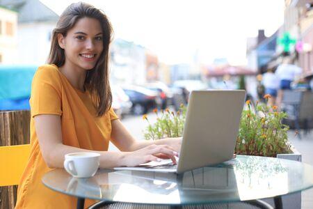 Smiling woman using laptop in cafe. Concept of entrepreneur, businesswoman, freelance worker Foto de archivo