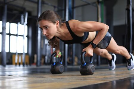 Portrait of a muscular woman on a plank position with kettlebell at gym