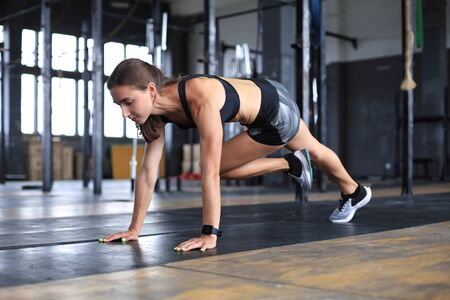 Portrait of a muscular woman doing planks on gym floor