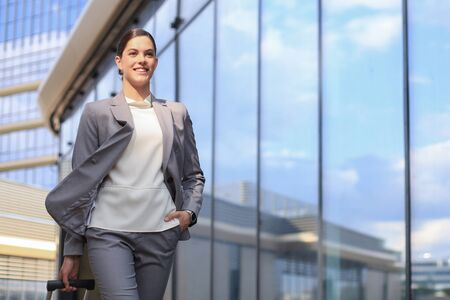 Portrait of successful business woman in suit looking away while walking outdoors Stock Photo