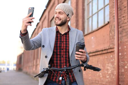 Handsome young man in grey coat and hat walking standing the street drinking coffee and taking selfie
