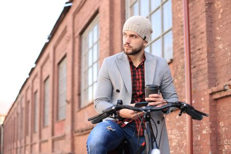 Handsome young man in grey coat and hat looking at phone while sitting on his bicycle