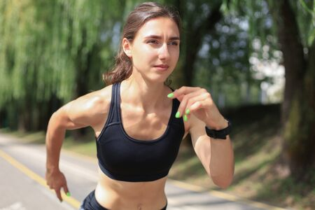 Young woman in sports clothing running while exercising outdoors Stock fotó