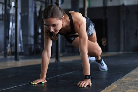 Portrait of a muscular woman doing planks on gym floor.