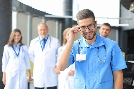 Doctor sonriente sosteniendo la tableta frente a su equipo médico Foto de archivo