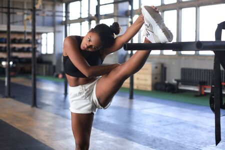 Young sporty woman stretching at the gym