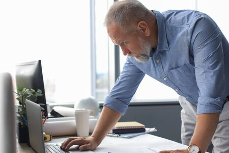 Senior businessman with a stylish short beard working on laptop computer at his office desk