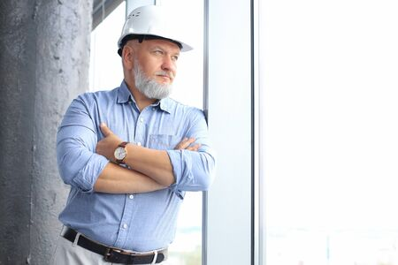 Thoughtful mature architect wearing hardhat and looking away while standing near the window in new modern building Banco de Imagens