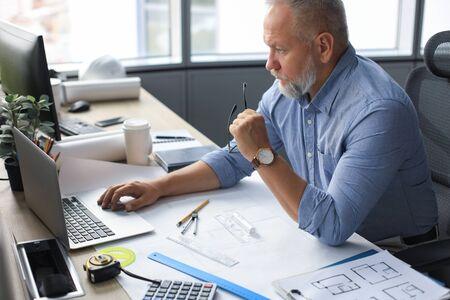 Senior Geschäftsmann mit einem stylischen kurzen Bart, der an seinem Schreibtisch an einem Laptop arbeitet