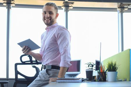 Young modern business man working using digital tablet while sitting in the office