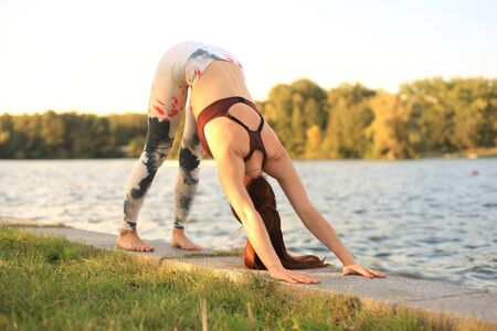 Young redhead sports woman make stretching yoga exercise outdoors
