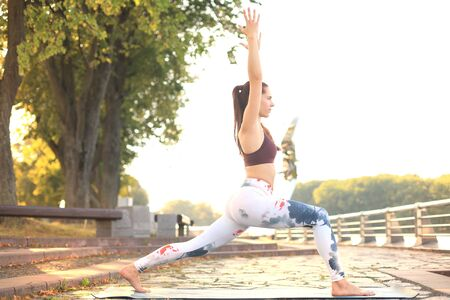 Sporty concentrated woman practicing yoga, standing in anjaneyasana pose, working out in park on sunset