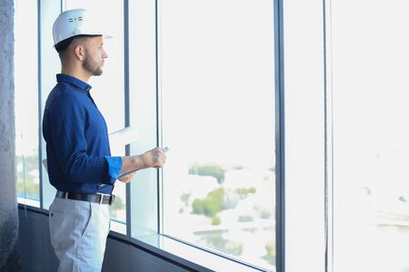Confident young business man in shirt examining blueprint while standing against a window at office