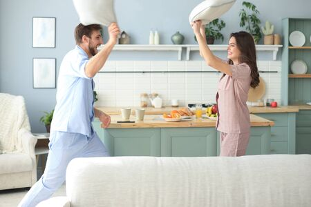 Happy loving couple having fun while having a pillow fight in the living room