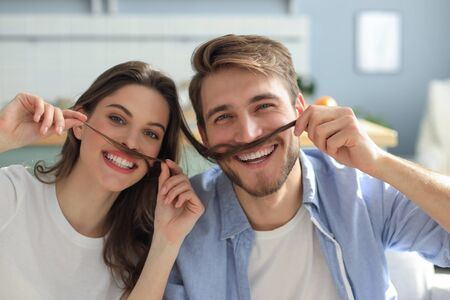 Portrait of cute young playful couple teasing with fake mustache sitting in sofa Imagens