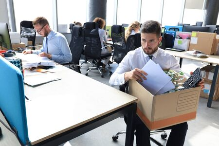 Sad dismissed worker are taking his office supplies with him from office.