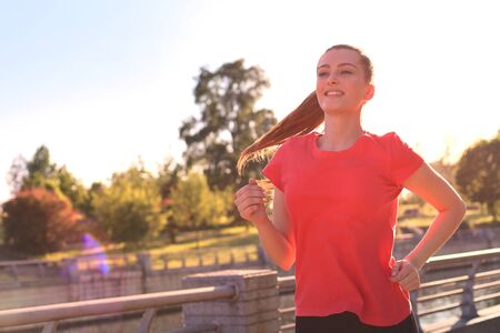 Beautiful young woman in sports clothing running while exercising outdoors