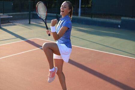Woman tennis player showing yes gesture after winning point, successful game