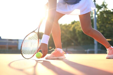 Tennis player raises a tennis ball from the clay court during the game Banco de Imagens