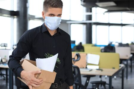 Dismissal employee in an epidemic coronavirus covid-19. Dismissed worker going from the office with his office supplies Stock fotó