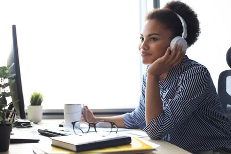 Young african american woman having a break and listening music in headphones sitting on working place