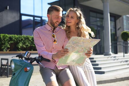 Young happy loving couple looking at map and sitting on scooter