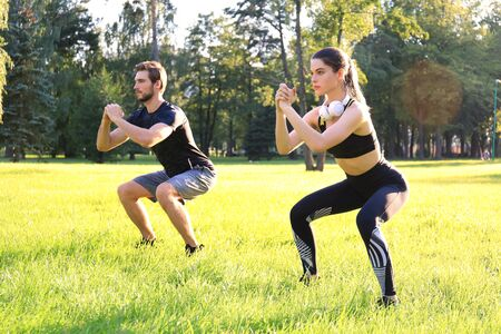 Young sporty man and woman doing workout and squatting together in green park during summer sunny day Banco de Imagens