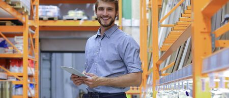 portrait of a smiling young warehouse worker working in a cash and carry wholesale store Banque d'images